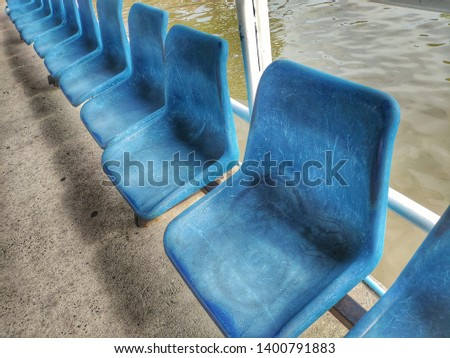 Old blue chairs arranged in long rows near by river.
