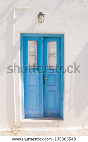 Old blue door on the whitewashed wall. Background.