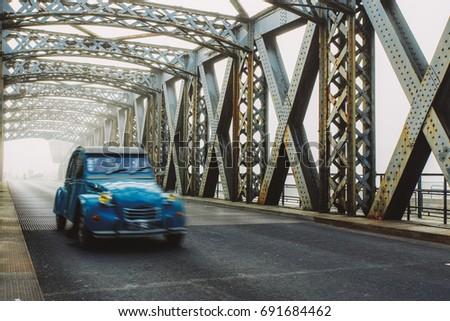 old blue vintage car driving on ...