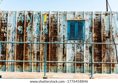 Old blue window on a rusty metal wall. Old Doc facade. Rusty metallic grille and colorful rusty iron wall. Rusty cargo container texture.