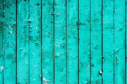 Old boards with cracked cyan paint. Textured wooden old background with vertical lines. Wooden planks for your design. Green-blue many times painted old wall with lagged fragments of paint lagging