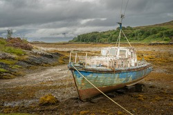 Old boat abandoned in  a bay in Scotland. Concept of sadness and loneliness