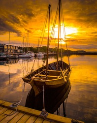 Old boat in harbor during sunset