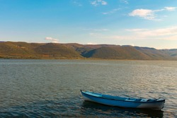 Old boat inside the sea is left deserted. A retro wooden blue boat docked on the lake. Hills are visible in distance on a beautiful day.