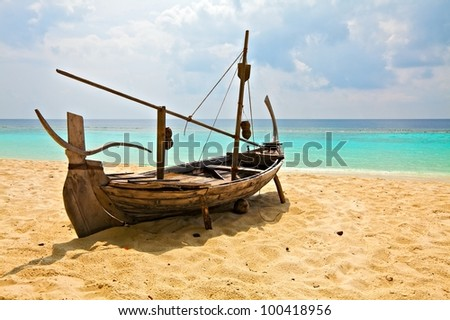 Old boat is on sandy beach, Maldives