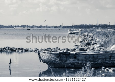Old boat is stranded on the coast, Mar Piccolo in Taranto, we are in southern Italy, on the horizon you can see the chimneys of the steel factory, horizontal shot, monochrome picture.