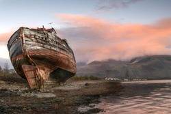 Old Boat on Caol Bay with Ben Nevis in the background, coverd by the glow of the evening sunset over the clouds.