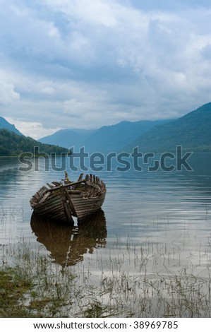 Old boat skeleton on the mountain lake in the hazy morning