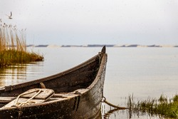 old boat stands in calm waters