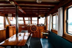 Old boat, steering wheel from brass and wood. Ship rudder. Sailboat helm, interior of an old schooner, inside the cabin of a sea ship