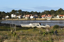 Old boat stranded on Cap-Ferret beach with the fishing village in the background