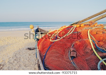 Old boat with fishing net on sandy shore. In Goa