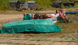 Old boats all covered up, rusty boat winches and fishing shacks all on the beach at Pakefield, Lowestoft.