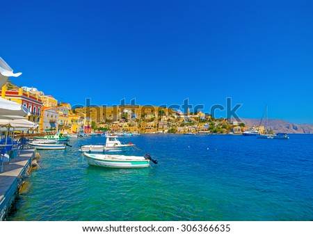 Old boats docked in the gulf of Symi island in Greece