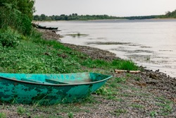 Old boats made of wood and metal on the river Bank among rocks and vegetation. Parked water transport in nature. Simple landscape.