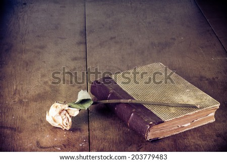 Old book and dried flower on grunge vintage wooden table