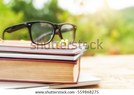 Old book and eye glasses for read and write over blurred nature outdoor background with copy space,selective focus ,education concept