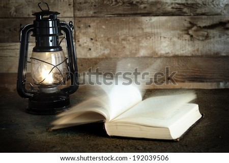 Old book and kerosene lamp on table