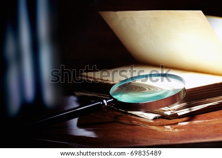Old book and magnifier glass on a dark background as a symbol of knowledge and science - stock photo