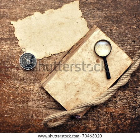 Old book, compass and magnifying glass on wood background