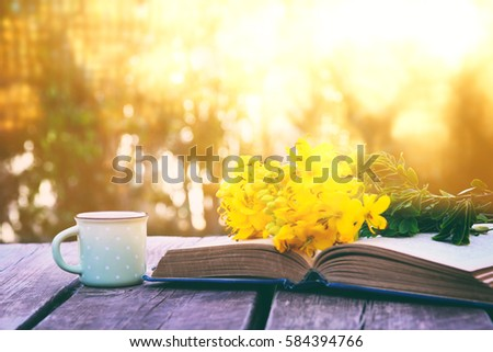old book, cup of coffee next to field flowers on wooden table outdoors at afternoon. selective focus #584394766