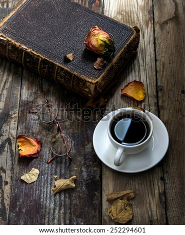 Old book , glasses,dried flower ,and leaves on a wooden table