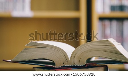 Old book in library. Book stack in the library room and blurred bookshelf for business and education background, back. Education concept.