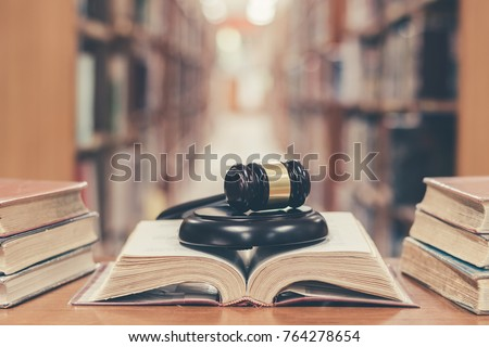 Old book in library with judge gavel on open law textbook in court archive text collection study room for copyrights day and international legal rights concept