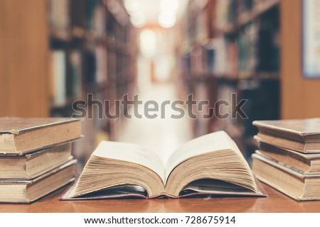 Old book in library with open textbook, stack piles of literature text archive on reading desk, and blur aisle of bookshelves in school study class room background for education learning concept #728675914