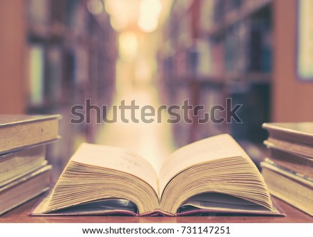 Old book in library with open textbook, stack piles of literature text archive on reading desk, and blur aisle of bookshelves in school study class room background for education learning concept #731147251