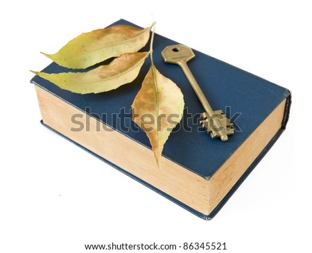 Old book, key and autumn leaves isolated on white
