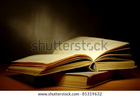 old book on a dark background and light beam