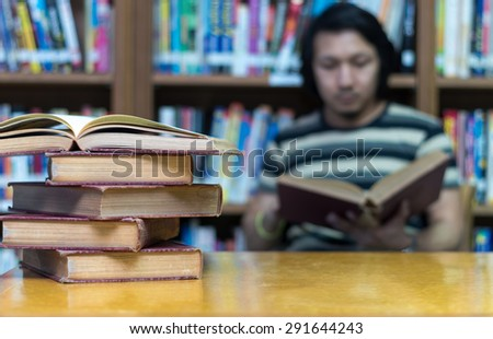 old book on the desk in library with the man reading the book background