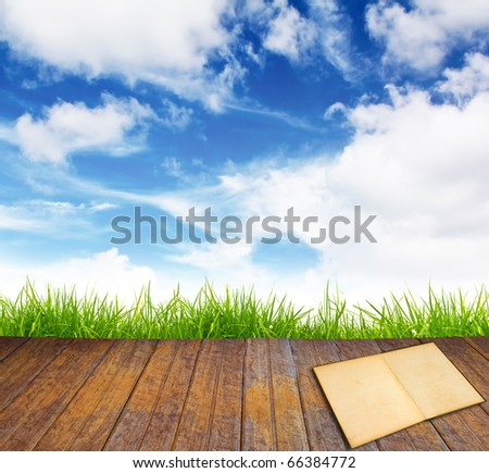 Old book on wood floor with green grass and blue sky.