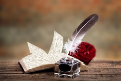 old book with a rose, feather and ink bottle isolated on white background, feather pen and inkwell