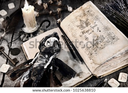 Stock Photo Old book with evil spells, scary doll, rune and burning candle on planks. Halloween, occult, esoteric and wicca concept. Vintage background