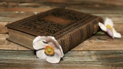 old book with flower on a wooden table