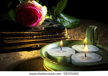 old book with rose and three candles on old table with mystic lightning