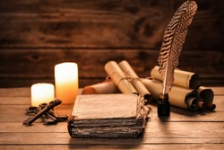 Old book with scrolls, feather, keys and candles on wooden background