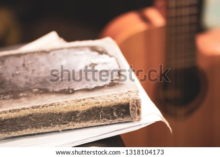 old book with songs and guitar on stage, preparation for the concert of the author's song #1318104173
