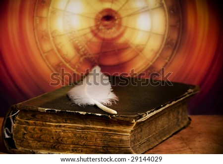 old book with white feather over astrological background