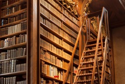 Old bookcase with the leather-bound book covers in the library of Vienna, Austria