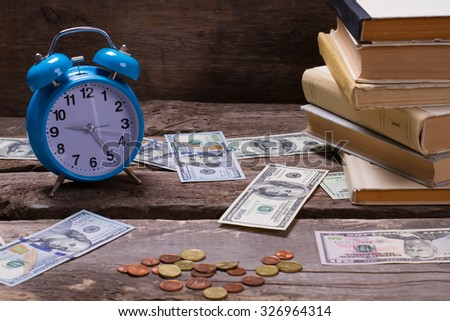 Old books, alarm clock and money on a vintage wooden background. Life goals.
