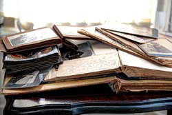 Old books, albums and photos on antique table.