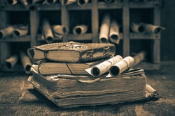 Old books and antique scrolls in library on wooden table