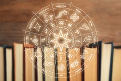 Old books and illustration of zodiac wheel with astrological signs on wooden background