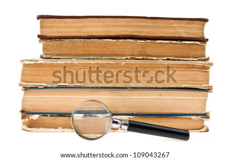 old books and magnifying glass on a white background