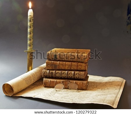 old books and map of 17 th century, enlightened in the candle