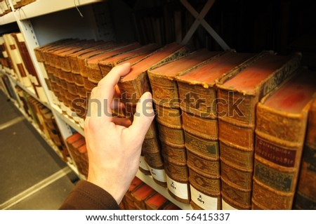 old books in a library with hand showing education concept