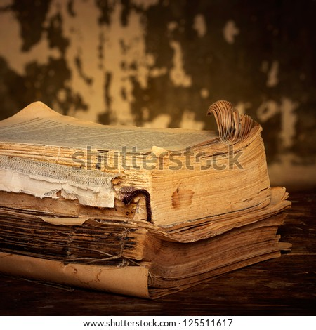 Old books of the Old binder are stacked on a wooden surface